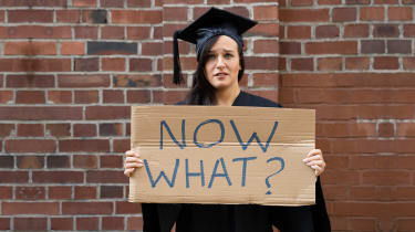 Confused student in a graduation gown holding a sign that says 'Now what?'