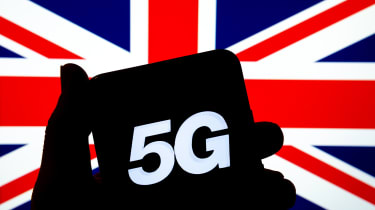 "A shadow of hand holding a smartphone with ""5G"" displayed on screen. UK flag is seen in the background."