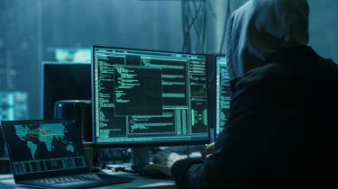 A man in a hoodie sitting in front of a computer with hacking software running on it
