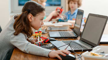 A schoolgirl using a laptop to program a robot made of plastic bricks