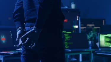 A man in handcuffs standing in front of computer equipment in a darkened room