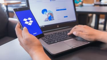 The Dropbox logo and website displayed on a smartphone and laptop, respectively
