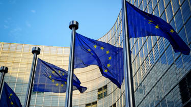 A series of European Union flags on show in front of a huge office building and a blue sky