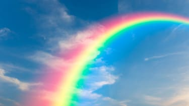 Image of a rainbow arching across a blue sky
