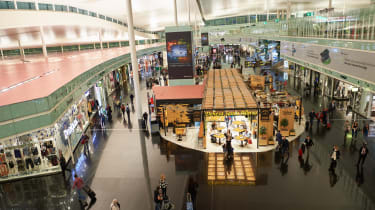 A shot of the retail section of Barcelona-El Prat Airport from above, with passengers walking around with