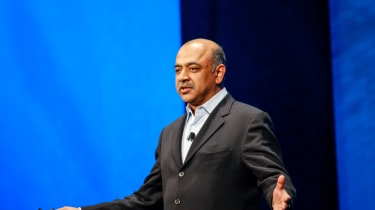 IBM CEO Arvind Krishna delivers a speech in front of a blue backdrop