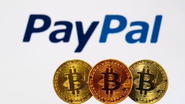 Three physical coins with the branded with the Bitcoin logo in front of the PayPal logo