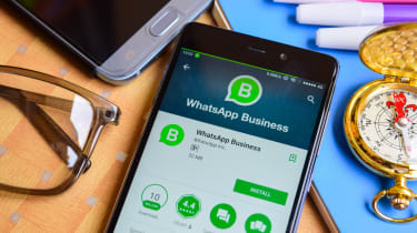 The WhatsApp Business app shown on an Android device on a desk surrounded by other items
