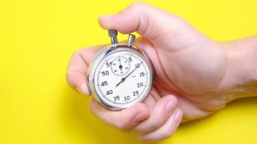 A hand holding a mechanical stopwatch on a yellow background