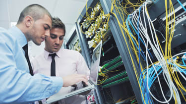 Two engineers looking at servers with lots of messy cables