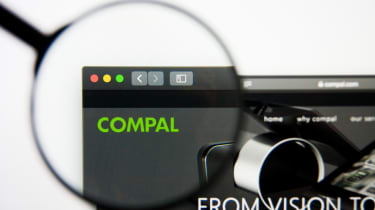 A magnifying glass focused on the Compal logo on the company's website
