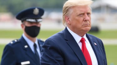 President Donald Trump escorted by a guard