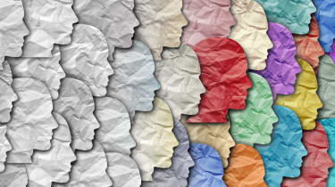 Dozens of overlapping paper head cutouts facing right fading from white to multicoloured