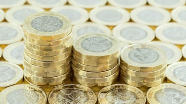 Three piles of pound coins surrounded by another layer of pound coins