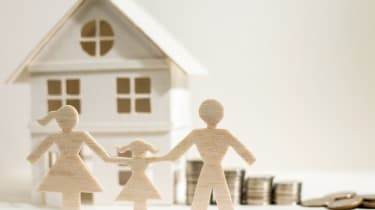 Cutout family in front of house and coins