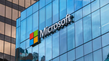The Microsoft logo as seen in large print fixed onto a glass building