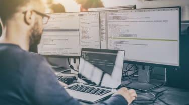 Man writing code on a laptop