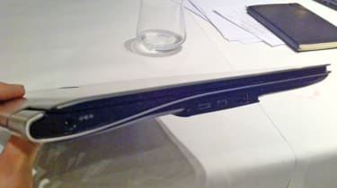 The Samsung 900X3A in hand with some of its flip-down ports visible