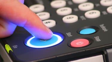 fax machine with send button pressed