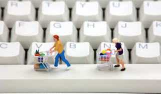 Shoppers with trollies on computer keyboard