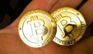 Two Bitcoins in a person's hands