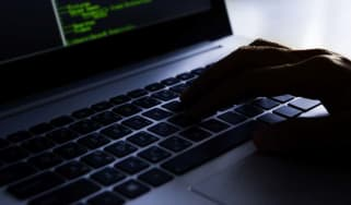 A hand typing on a keyboard in a malicious manner