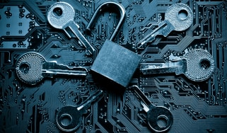 A padlock on a motherboard surrounded by keys