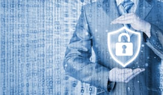 Abstract cyber security image of a man holding a symbol of a padlock inside a shield