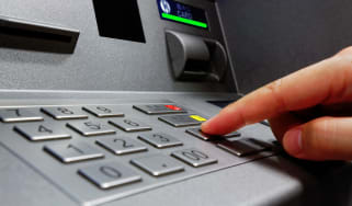 Person entering their PIN number into an ATM machine