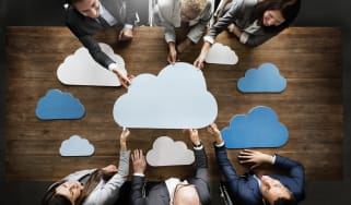 group of people stand around a table with multiple clouds around them