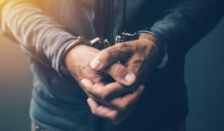 Closeup of a criminal's wrists in handcuffs