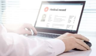 NHS doctor examining digitised medical records on a laptop