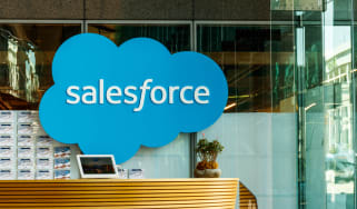 The Salesforce logo on a glass wall in an office building