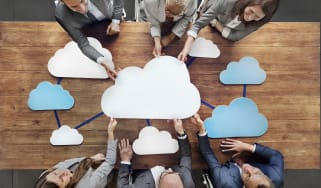 Several business people holding a network of 2D clouds over a wooden table