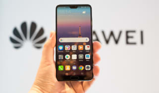 A hand holding a Huawei smartphone with the Huawei logo in the background
