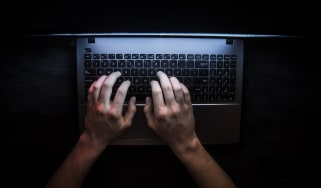 Person types on laptop in the dark