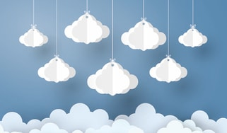 Several small clouds hanging from strings against a blue backdrop