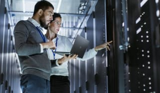 The image of two individuals in a server room having a discussion