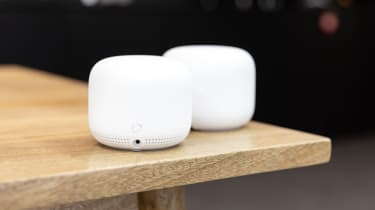 Two Google Nest smart speakers on a wooden table