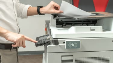 An office worker using a large printer