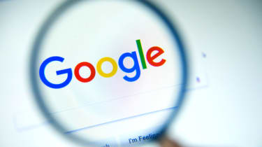 The Google logo under a magnifying glass