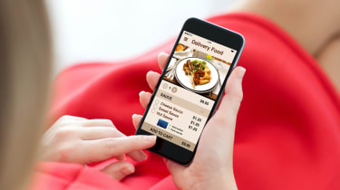 A woman looking at food on a delivery app on her smartphone