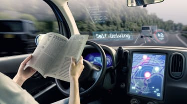 A woman reading a book in the driver's seat while the car drives itself