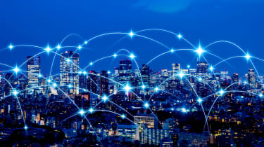 A city skyline connected by networks to represent IoT