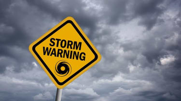 """""""Storm warning"""" sign with clouds behind it"""