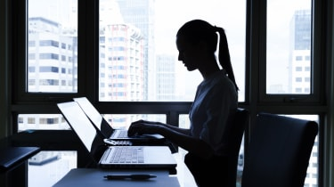 Silhouette of a woman sitting at a desk in front of a computer