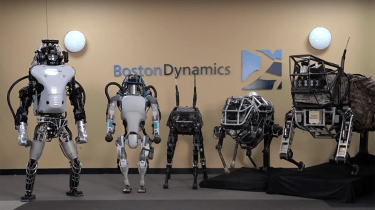 Five robots in front of  Boston Dynamics sign