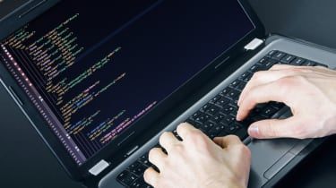 Man typing code on a laptop