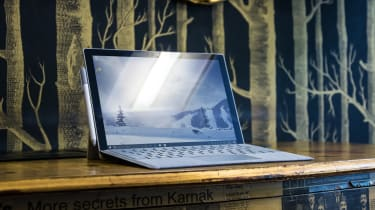 Microsoft's Surface Pro tablet on a desk in front of a forest patterned wall