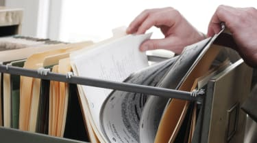 A person rifling for files in an old-style filing cabinet